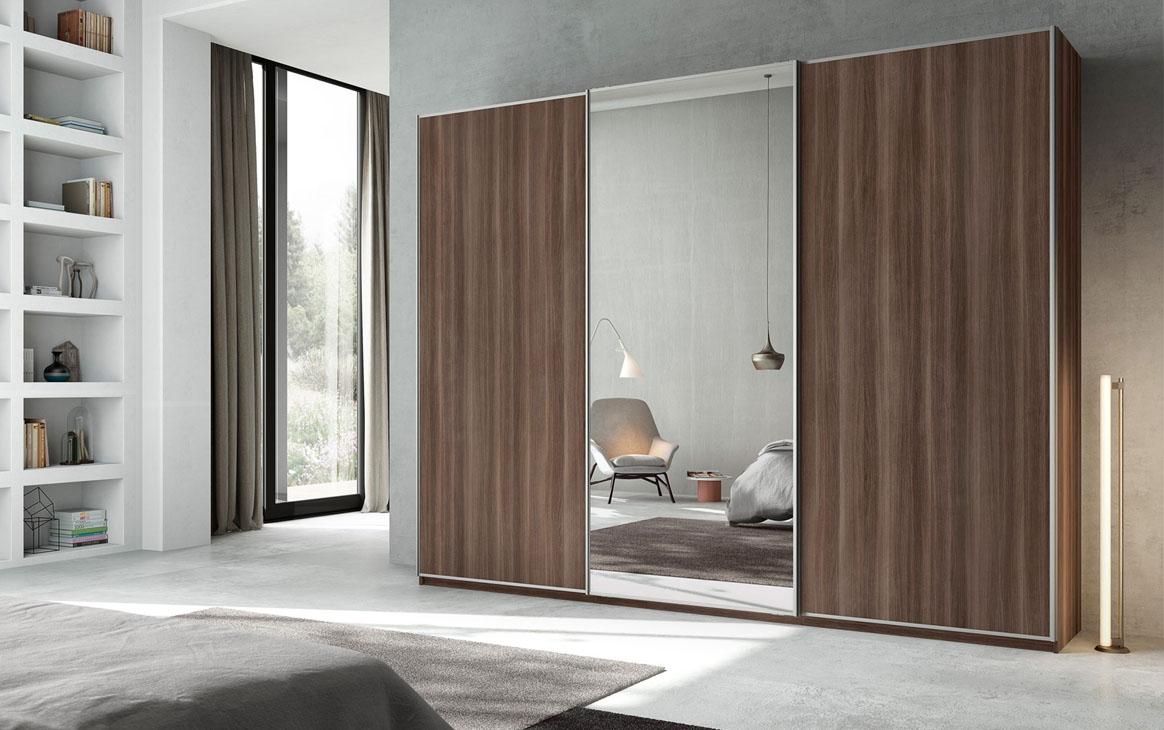 Armario con puertas correderas que incorpora espejo en uno de los frentes. Diferentes acabados